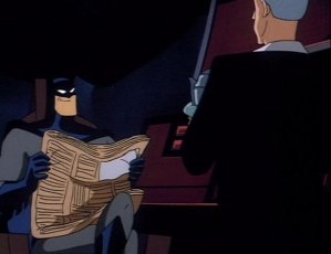 Batman sits in the Batcave holding a newspaper, smirking at Alfred.